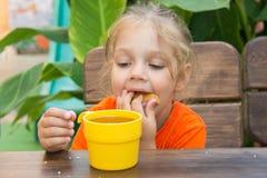 Petit pain bourré drôle de fille de quatre ans dans sa bouche et regards à un verre de thé Photographie stock libre de droits