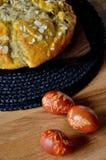 Petit pain croisé de Pâques avec les oeufs colorés naturels Photo stock