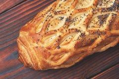 Petit pain cuit au four avec la pâte feuilletée, arrosée avec des clous de girofle sur un fond en bois foncé Plan rapproché Fond  images stock