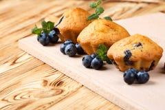 Petit pain cuit au four fait maison avec des myrtilles, baies fraîches, menthe sur le fond en bois L'espace vide pour le texte Images stock