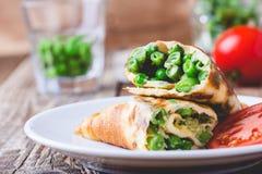 Petit pain d'omelette d'oeufs avec remplir de haricots verts et de pois Photos libres de droits