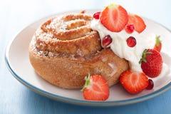 Petit pain de cannelle doux avec de la crème et la fraise Photo libre de droits