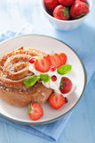 Petit pain de cannelle doux avec de la crème et la fraise pour le petit déjeuner Photographie stock