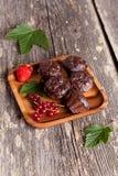 Petit pain de chocolat avec la groseille rouge sur le fond en bois Images stock