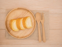 Petit pain de gâteau de vue supérieure dans le plat en bois avec la cuillère en bois et fourchette sur la table en bois beige, fo Photos stock