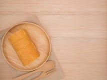 Petit pain de gâteau de vue supérieure dans le plat en bois avec la cuillère en bois et fourchette sur la table en bois beige, fo Photographie stock libre de droits