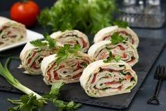 Petit pain de Lavash avec le poulet fumé, les tomates, le fromage et les verts situés sur un fond foncé image libre de droits