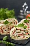 Petit pain de Lavash avec le poulet fumé, les tomates, le fromage et les verts situés sur un fond foncé photos stock