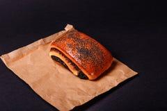 Petit pain de pavot sur le fond noir Savoureux faites cuire au four images libres de droits
