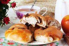 Petit pain de petit pain avec le raisin sec de pomme et de cannelle dans une vie immobile du plat lumineux Photographie stock libre de droits