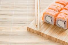 Petit pain de Philadelphie de sushi sur un conseil en bois Cuisine japonaise Image stock