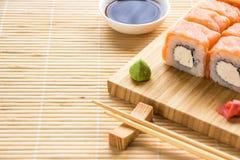 Petit pain de Philadelphie de sushi sur un conseil en bois Cuisine japonaise Image libre de droits