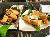 Petit pain de ressort de poulet d'apéritif et plat blanc de samosa sur la table au restaurant Foyer sélectif Voir les mes autres  Photo libre de droits
