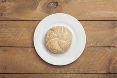 Petit pain de sésame de plat et de bois Image stock
