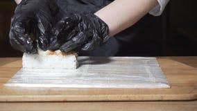 Petit pain de sushi à cuire en gros plan de riz Vue Plan rapproché de chef de cuisine orientale dans les gants préparant des peti images libres de droits