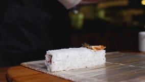 Petit pain de sushi à cuire en gros plan de riz Vue Plan rapproché de chef de cuisine orientale dans les gants préparant des peti photos stock