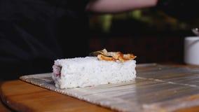 Petit pain de sushi à cuire en gros plan de riz Vue Plan rapproché de chef de cuisine orientale dans les gants préparant des peti image stock