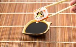 Petit pain de sushi avec le concombre et le fromage saumonés avec des baguettes Photographie stock