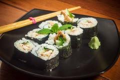 Petit pain de sushi avec le thon et le concombre du plat noir Images libres de droits