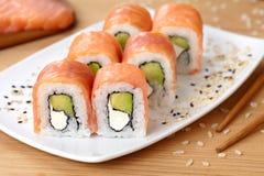 Petit pain de sushi avec les saumons fumés, avocat, doucement image stock