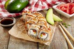 Petit pain de sushi saumoné et fumé d'anguille avec Daikon mariné image libre de droits