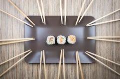 Petit pain de trois sushi dans le plat avec plusieurs de baguettes sur la table en bois photos stock