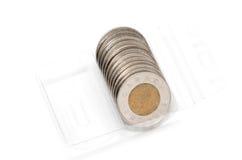 Petit pain en plastique tenant deux pièces de monnaie du dollar Photo libre de droits