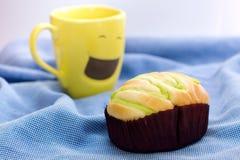 Petit pain et tasse de café jaune image stock