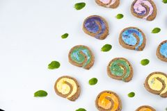 Petit pain minimal coloré crémeux délicieux de gâteau sur le fond blanc photographie stock