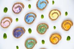 Petit pain minimal coloré crémeux délicieux de gâteau sur le fond blanc photographie stock libre de droits