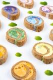 Petit pain minimal coloré crémeux délicieux de gâteau sur le fond blanc photo stock