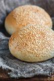 Petit pain rond, petit pain de sésame, petits pains de pain Pain savoureux d'hamburger avec le sésame sur en bois, fond de toile  Photos libres de droits