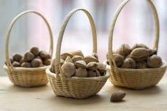 Petit panier trois en osier avec des amandes, des noix et des noisettes Photo libre de droits