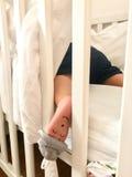 Petit petit garçon dormant dans son berceau avec un visage fermé de yeux peint sur son pied gauche Photo libre de droits