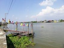 Petit pilier avec le drapeau jaune et le drapeau de la Thaïlande sur le fleuve Chao Phraya image libre de droits