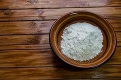 Petit plat avec de la farine sur la table photographie stock