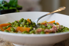 Petit pois a la Francaise in bowl with spoon Stock Images