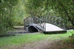 Petit pont arqué en bois sensible au-dessus d'un courant tranquille profondément en vieux, épais parc de vacances Photographie stock libre de droits