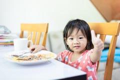 petit pouce d'apparence d'enfant de b?b?, mangeant et appr?cier le petit d?jeuner seule photo libre de droits