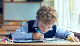 Petit préadolescent bouclé s'asseyant à la table et faisant des devoirs à l'école image libre de droits