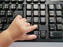 Petit pressing asiatique de doigt du ` s de bébé sur un clavier d'ordinateur photos stock