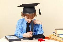 Petit professeur dans le chapeau scolaire regardant par le microscope son bureau Image stock