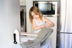 Petit repasser et pantalons de fille dans la cuisine Photo stock