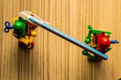 Petit robot deux tenant un stylo sur le plancher photographie stock libre de droits