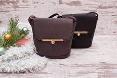 Petit sac à main femelle brun et noir sur un fond en bois, branche de sapin avec des décorations Photo stock