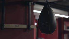 Petit sac de sable en cuir noir pour une formation de boxeur pendant du plafond dans le gymnase Longueur courante pneumatique banque de vidéos