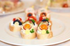 Petit sandwich avec la diffusion, légume, tomate jaune, persil, concombre du plat blanc Image libre de droits