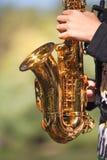 Petit saxophone d'or dans des mains photos libres de droits