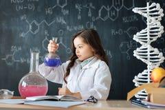 Petit scientifique inventif étudiant la chimie dans le laboratoire photographie stock
