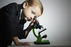 Petit scientifique regardant dans le microscope Little Boy Enfant Éducation Image stock